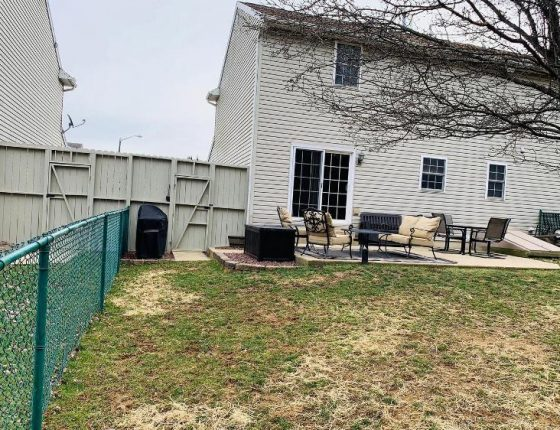 backyard lawn and green fence of new home for sale