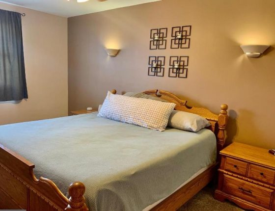 bed sitting beside furniture piece and beneath wall decorations and lights