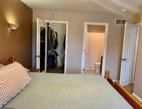 queen size bed sitting parallel to walk in closest and bathroom