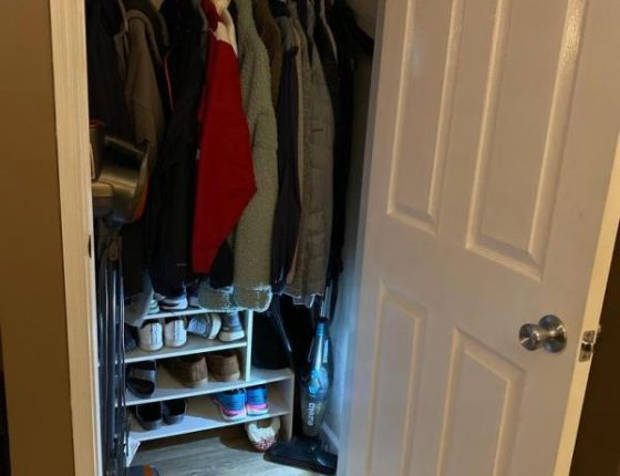 single closet filled with clothes and shoes in new home for sale