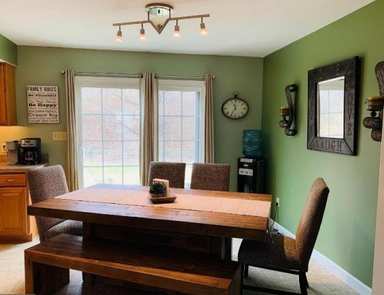 wood dining room table surrounded by green walls and sliding glass door in new home for sale