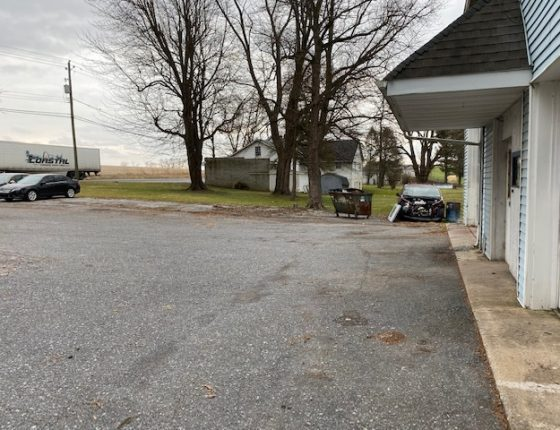 front driveway with dumpster and wrecked car at auto garage for rent