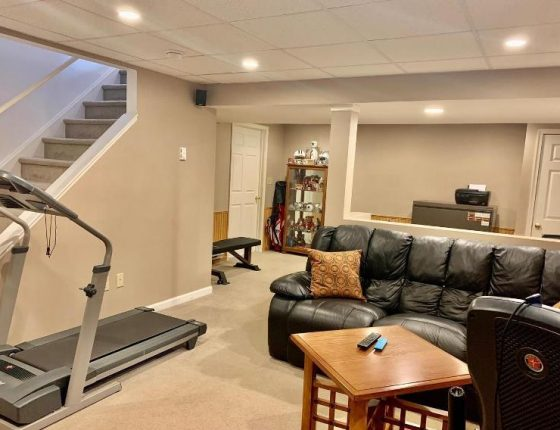 leather couch and treadmill in basement of new home for sale