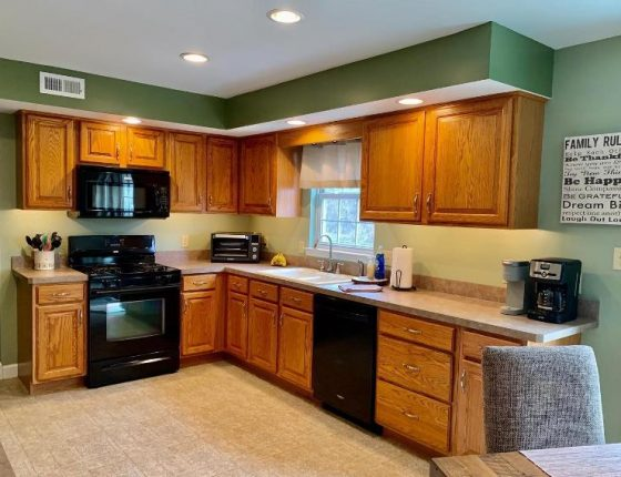 brown kitchen cabinets and black kitchen appliances in new home for sale