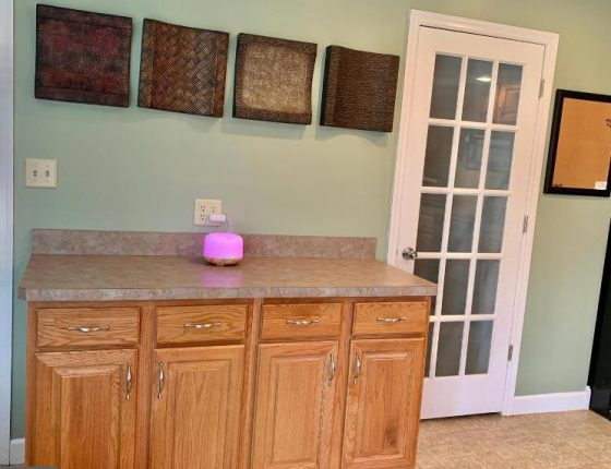 kitchen cabinets sitting beneath wall decorations and beside white door