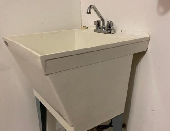 grey laundry room sink in new home for sale