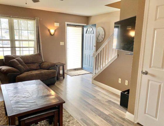 living room furniture sitting on hardwood floor next to open front door