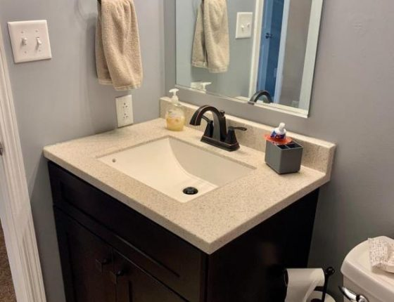 modern sink in corner of bathroom with soap and toothpaste holder sitting on top