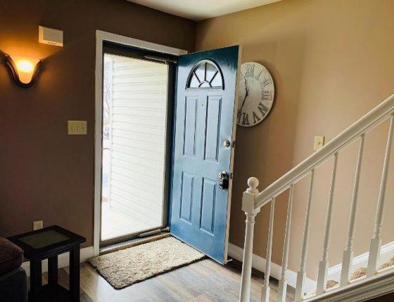 open front door partially blocking view of decorative clock