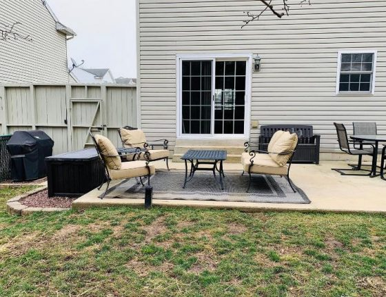 outdoor patio furniture sitting on carpet in front of sliding glass door