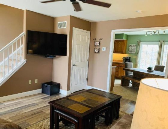 television set and living room furniture sitting next to kitchen in new home for sale