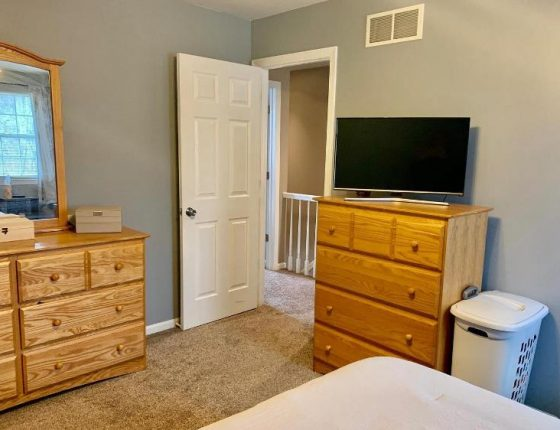 upstairs bedroom furniture and white open door leading to hallway