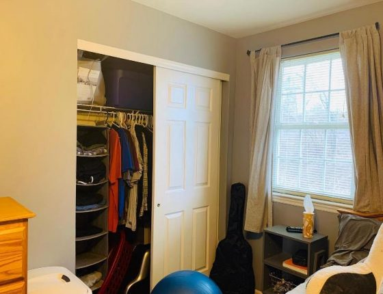 upstairs closet filled with clothes next to guitar case and window