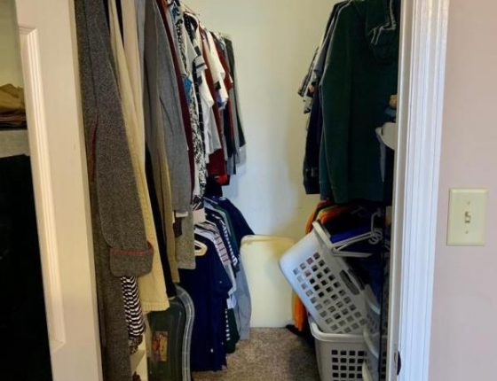 large walk in closest filled with clothes and hampers in new home for sale