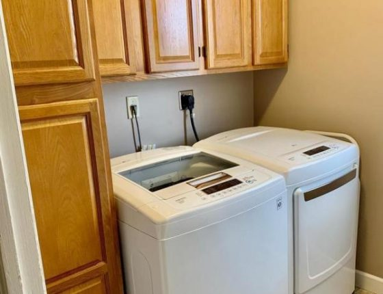 washer and dryer sitting beneath cabinetry in wilson school district home for sale